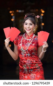 Portrait of Chinese woman wear traditional dress cheongsam and holding Red envelope or gife voucher for reward at chinese shrine in chinese new year, China Girl.