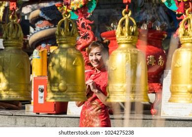 Portrait Chinese woman wearing traditional costume during Chinese New Year in temple.Female with China traditional dressing red cheongsam.  Young girl with Lunar Chinese new year culture.