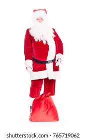 Portrait of Christmas character Santa Claus in traditional costume with red sack on white background