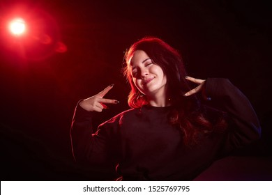 Portrait of chubby teen girl illuminated by red light and black background. Model in a photo shoot with colored light
