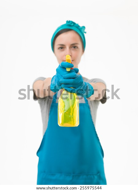 portrait of cleaning woman aiming spray bottle in front of her, on white background