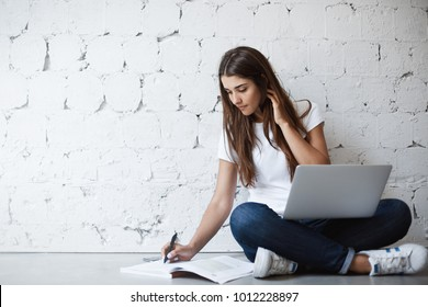 Portrait of clever attractive female translator, sitting on floor with laptop on crossed hands, making notes in book, touching her neck with hand while leaning on wall. Girl tries to finish project.