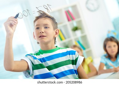 Portrait of clever boy doing sums on transparent board with schoolmates on background
