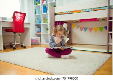Portrait of clever little girl reading book on the floor at home