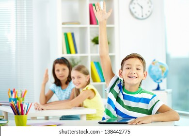 Portrait of clever schoolboy raising hand at workplace with two classmates behind