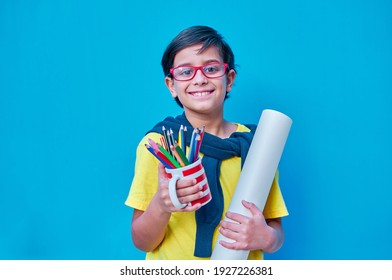 A Portrait of a clever and studious boy with red glasses, in a yellow T-shirt, holding in his hand a cup with lots of colored pencils and a roll of painting paper. On blue background. Copy space