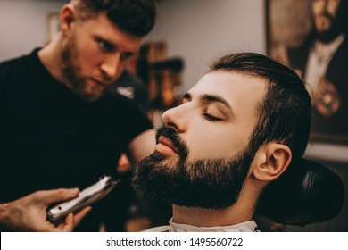 portrait of client during beard and hair grooming in stylish barber shop. Bearded barber forms the shape of a customer's beard with a trimmer.Selective focus, noise effect