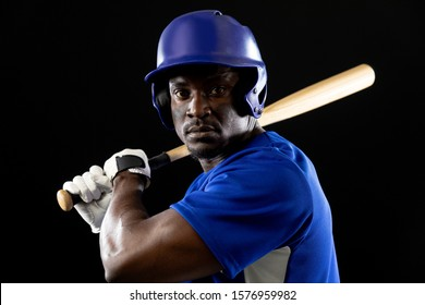 Portrait close up of an African American male baseball player, a hitter, wearing a team uniform and a helmet, ready to swing a baseball bat