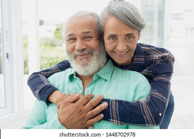 Portrait close up of African-American  couple hugging each other inside a room. Authentic Senior Retired Life Concept