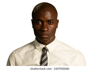 Portrait close up of a bald young African American businessman wearing a shirt and tie, looking straight to camera