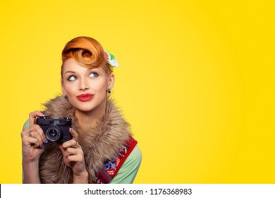 Portrait close up of beautiful young woman pinup girl thinking looking away, up holding camera isolated on yellow wall background with copy space. Human face expression emotions feeling body language