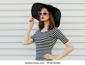 Portrait close up of beautiful young woman wearing a black summer straw hat on a white background