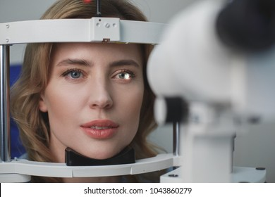Portrait of close up concentrated female face examining eyesight with equipment in hospital. Optometry concept