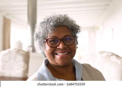 Porträt, Nahaufnahme einer glücklichen älteren Afroamerikanerin, die eine Brille trägt, die mit der Kamera lächelt. Familie genießt Zeit zu Hause, Lifestyle-Konzept