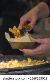 portrait close up of man serving chips into greaseproof paper and box with tongs