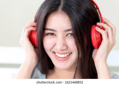 Portrait close up pretty teenage woman wearing red bluetooth headphone, Dance and smiley for listening music with joyful