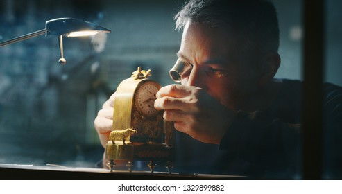 Portrait close up of a professional watchmaker repairer working on a vintage mechanism clock in a workshop.