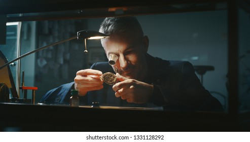 Portrait close up of a professional watchmaker repairer working on an old vintage pocket watch in a workshop.