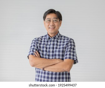 Portrait close up shot of middle aged asian male model with short black hair wearing blue plaid shirt with stand smiling fold his arms in smart pose on white background.