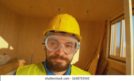 PORTRAIT, CLOSE UP, DOF: Young contractor wearing protective gear stands in a modern prefabricated wooden house. Handsome bearded builder smiles while taking a break from work on cross-laminated house