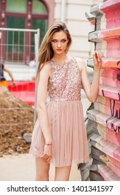 Portrait close up of young beautiful blonde woman in pink dress, summer street