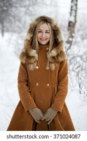 Portrait close up of young beautiful blonde woman, on winter street background