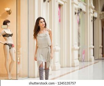 Portrait close up of young beautiful brunette woman in beige dress walkin in the shop