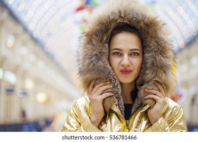Portrait close up of young beautiful brunette woman in golden fur coat, indoor shop