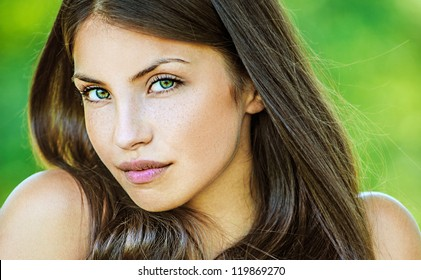 Portrait close up of young beautiful woman, on green background summer nature.