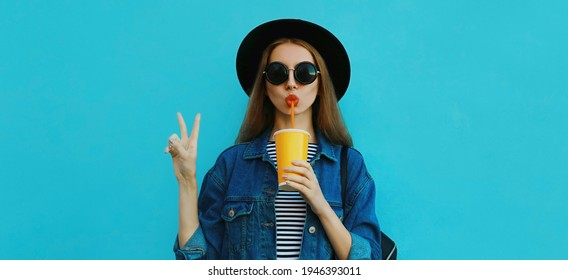 Portrait close up of young woman drinking a juice wearing a black round hat, denim jacket on a blue background