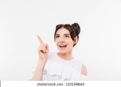 Portrait closeup of amazed young woman with double buns hairstyle and dental braces smiling while pointing finger aside at copyspace isolated over white background