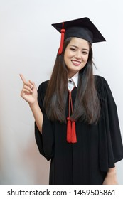 Portrait closeup. Asian beautiful smiley graduate graduated student girl young woman in cap gown on isolated white background wall. Celebrating graduation ceremony concept.