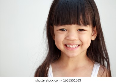 Portrait Closeup Asian kid girl aged 4 to 6 years old. Cute face, bright, long hair, smiling cute. Her smiles saw a strong, mature tooth. Make her smile beautiful, isoloate withe background