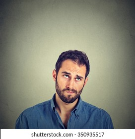 Portrait closeup funny confused skeptical man thinking looking up isolated on gray wall background with copy space above head. Human face expressions, emotions, feelings, body language