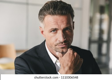 Portrait closeup of handsome businessman wearing white shirt and black suit touching chin and looking at camera while working in office room