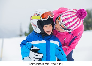 portrait closeup of happy smiling boy in ski goggles and a helmet with his mother