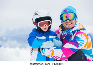 portrait closeup of happy and smiling father and son in ski goggles and a helmet