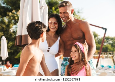 Portrait closeup of joyful european man and woman with kids smiling while resting near luxury swimming pool with deckchairs and umbrellas during vacation