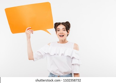 Portrait closeup of joyful sly girl 20s with double buns hairstyle holding empty placard for copyspace text isolated over white background