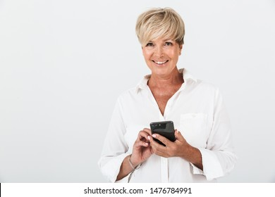 Portrait closeup of joyous adult woman with short blond hair smiling and holding cellphone isolated over white background in studio