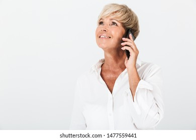 Portrait closeup of joyous adult woman with short blond hair smiling and talking on cellphone isolated over white background in studio