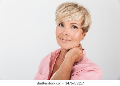 Portrait closeup of joyous middle-aged woman with short blond hair smiling at camera isolated over white background in studio