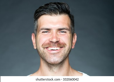 Portrait closeup of one handsome sensual shaved man with bristle smiling and looking forward in studio model posing on grey background, horizontal picture