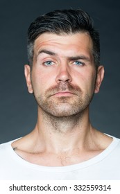 Portrait closeup of one handsome sensual shaved man with  bristle and eyebrow raised model looking forward in studio on grey background, vertical picture