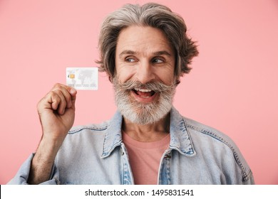 Portrait closeup of satisfied old man 70s with gray beard smiling while holding credit card isolated over pink background
