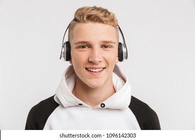 Portrait closeup of teenage boy 16-18 years old wearing hoodie and wireless headphones posing with happy smile isolated over white background