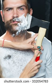 Portrait closeup young handsome sensual bearded man having shaved scrape chin with chopper foam frown studio play of light and shadow on black background, vertical picture