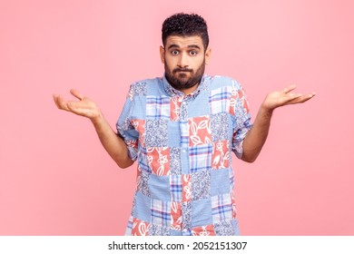 Portrait of clueless confused man in blue casual style shirt shrugging shoulders as doesn't know answer, can`t make decision, being uncertain, not sure. Indoor studio shot isolated on pink background.