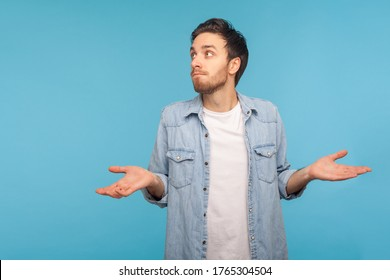 Portrait of clueless confused man in worker denim shirt shrugging shoulders as doesn't know answer, can`t make decision, being uncertain, not sure. indoor studio shot isolated on blue background