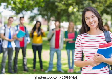 Portrait of college girl holding books with blurred students standing in the park